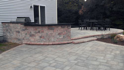 bi-level patio with seating area and an outdoor kitchen